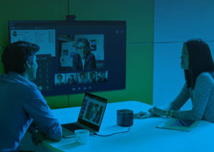 Two people in a small meeting room with a third person teleconferencing